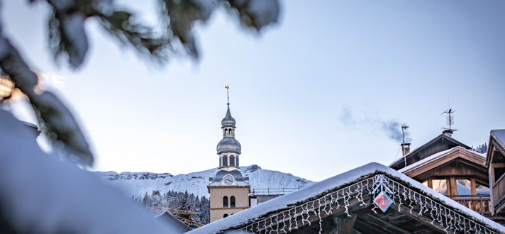 snow scene in foreground with a french church steeple in the centre of the image