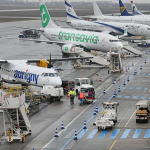 several planes parked up on a runway with airport vehicles and staff activity throughout